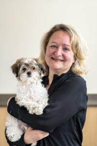blonde woman in black shirt holding Maltese dog