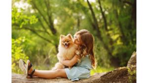 girl sitting on log with pomeranian dog on her lap